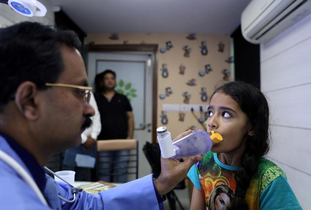 Dr. Dhiren Gupta, a pediatrician, demonstrates to his patient Akshra Quereshi (10) how to use a spacer device for her medication at a hospital in New Delhi, India, November 5, 2019. Picture taken November 5, 2019. REUTERS/Anushree Fadnavis