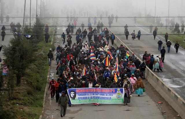 Supporters of ousted Bolivia's President Evo Morales carry a banner across the main avenue as they block roads in El Alto, on the outskirts of La Paz, Bolivia, November 15, 2019. REUTERS/David Mercado