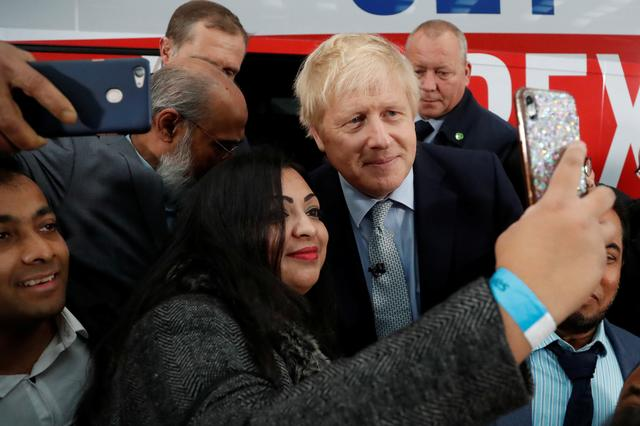 Britain's Prime Minister Boris Johnson poses for a picture with a supporter in front of the general election campaign trail bus in Manchester, Britain November 15, 2019. Frank Augstein/Pool via REUTERS