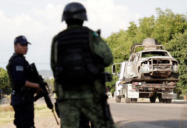 FILE PHOTO: A tow truck transports the wreckage of a police patrol car after an ambush by suspected cartel on police officers in El Aguaje, in Michoacan state, Mexico October 14, 2019. REUTERS/Alan Ortega/File Photo