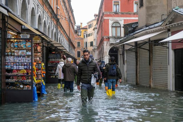 People walk in the flooded street during a period of seasonal high water in Venice, Italy, November 15, 2019. REUTERS/Manuel Silvestri