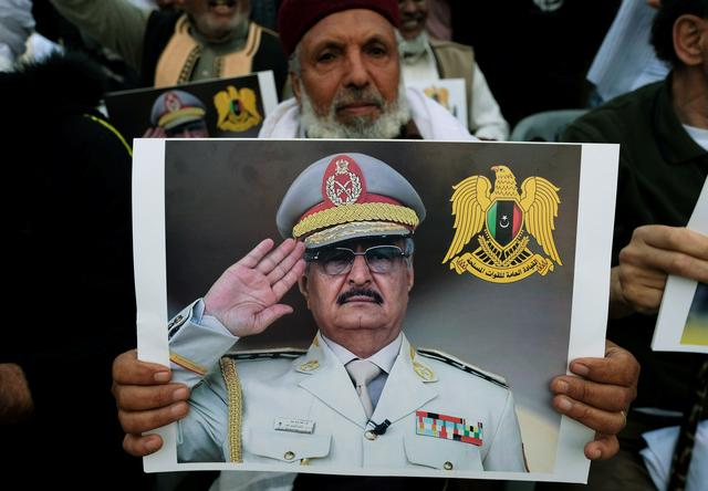 FILE PHOTO: A Libyan man carries a picture of Khalifa Haftar during a demonstration to support Libyan National Army offensive against Tripoli, in Benghazi, Libya April 12, 2019. REUTERS/Esam Omran Al-Fetori/File Photo