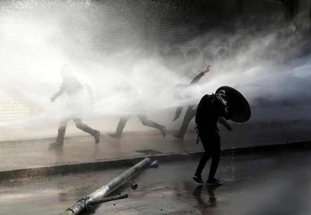 FILE PHOTO: A demonstrator takes cover from a spray of water during a protest against Chile's government in Santiago, Chile, November 15, 2019. REUTERS/Goran Tomasevic/File Photo