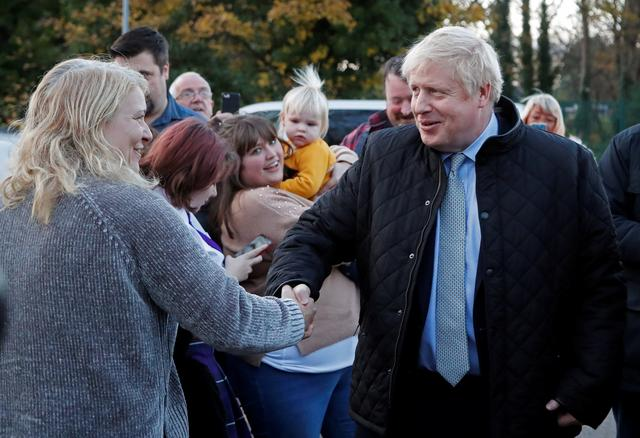Britain's Prime Minister Boris Johnson is greeted during a general election campaign trail stop at Thornton-Cleveleys railway station in Manchester, Britain November 15, 2019. Frank Augstein/Pool via REUTERS