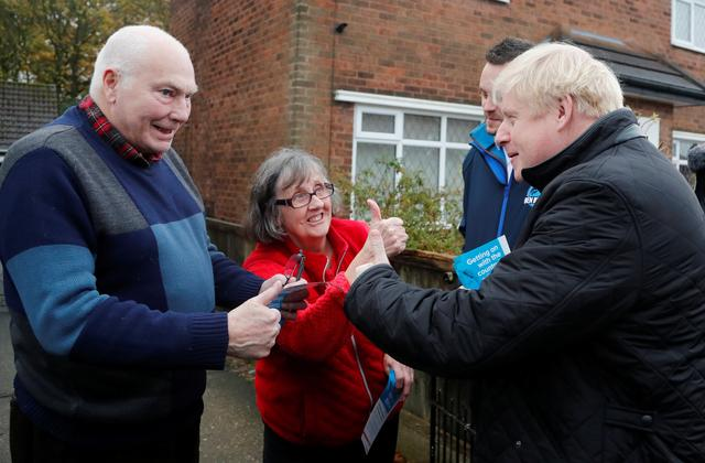 Britain's Prime Minister Boris Johnson with Conservative party candidate for the Mansfield constituency Ben Bradley speaks with people as they campaign in Mansfield, Britain, November 16, 2019. Frank Augstein/Pool via REUTERS