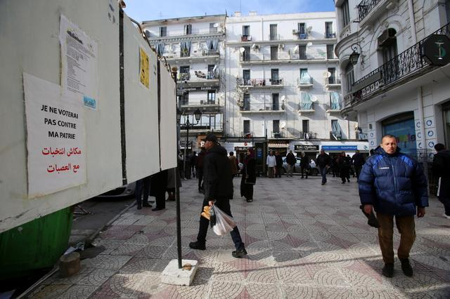 People walk past presidential election poster panels in Algiers, Algeria November 17, 2019. REUTERS/Ramzi Boudina