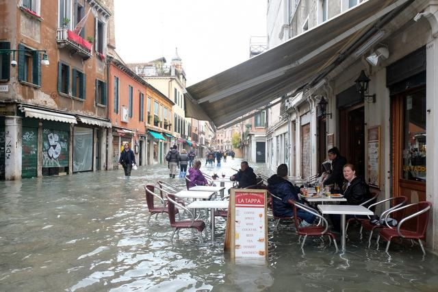 People sit at a cafe in a flooded street during a period of seasonal high water in Venice, Italy, November 17, 2019. REUTERS/Manuel Silvestri