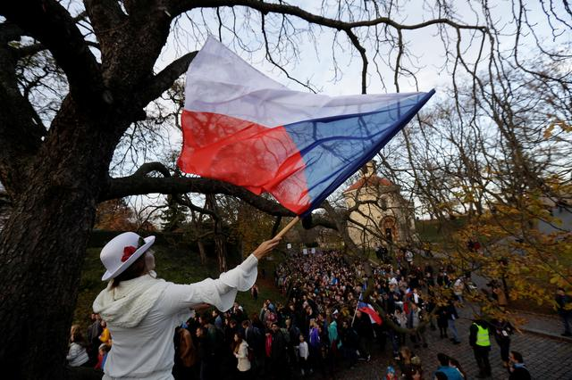 A woman waves a flag of Czech Republic during a reenactment of the 1989 protest march to commemorate the 30th anniversary of the 1989 Velvet Revolution in Prague, Czech Republic, November 17, 2019. REUTERS/David W Cerny