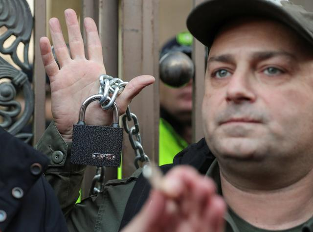 Opposition supporters chain the gate of the parliament during a rally to protest against the government and demand an early parliamentary election, in Tbilisi, Georgia November 17, 2019.  REUTERS/Irakli Gedenidze