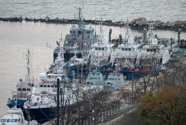 FILE PHOTO: Seized Ukrainian naval ships are guarded by Russia's Coast Guard vessels in the port in Kerch, near the bridge connecting the Russian mainland with the Crimean Peninsula, Crimea November 17, 2019. REUTERS/Alla Dmitrieva