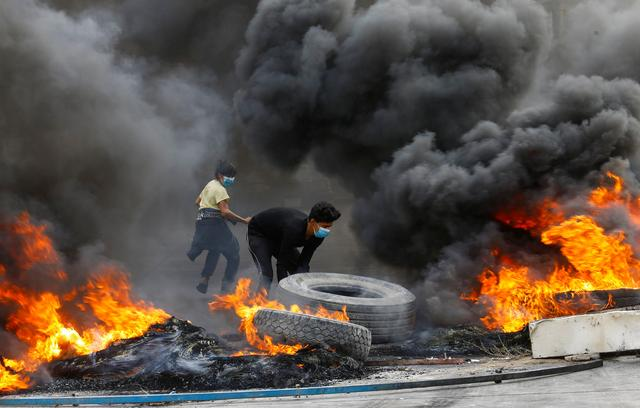 Iraqi demonstrators burn tires during the ongoing anti-government protests in Najaf, Iraq November 18, 2019. REUTERS/Alaa al-Marjani
