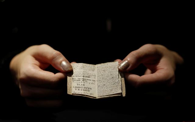 An employee displays the second issue of Young Men's Magazine, a miniature manuscript dated 1830, written by Charlotte Bronte when she was 14 years old, before being put on auction at Drouot auction house in Paris, France, November 18, 2019. REUTERS/Christian Hartmann