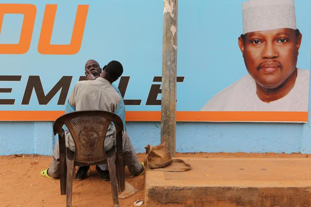 FILE PHOTO: A man gets a haircut and a shave in front of a campaign poster of incarcerated opposition candidate Hama Amadou in Niamey, Niger, February 15, 2016. Niger holds presidential and legislative elections on Sunday. REUTERS/Joe Penney/