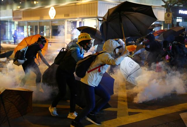 Anti-government protesters run from tear gas during clashes with riot police at Tsim Sha Tsui, in Hong Kong, China, November 18, 2019. REUTERS/Athit Perawongmetha