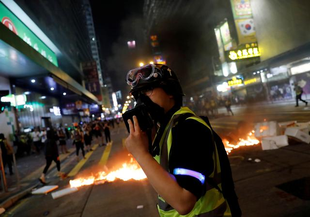 Pastor Alan Keung covers his face with a gas mask after riot police fired rounds of tear gas during an anti-government protest in Hong Kong, China November 2, 2019. REUTERS/Kim Kyung-Hoon
