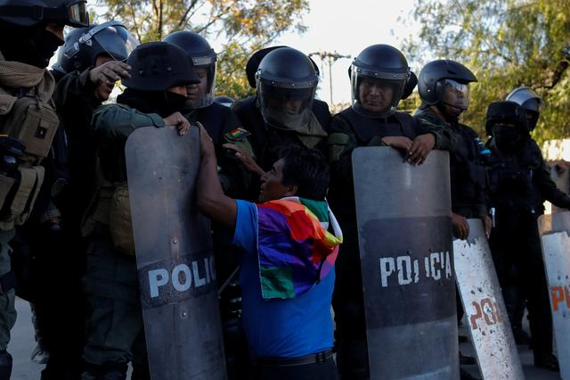 A supporter of former Bolivia's President Evo Morales kneels and gestures in front of members of the security forces during a demonstration in Cochabamba, Bolivia, November 18, 2019. REUTERS/Marco Bello