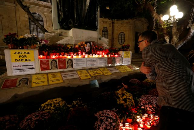 FILE PHOTO: A tourist looks at a makeshift memorial to assassinated anti-corruption journalist Daphne Caruana Galizia after an anti-corruption protest against the government of Prime Minister Joseph Muscat in Valletta, Malta, November 16, 2019. REUTERS/Darrin Zammit Lupi/File Photo