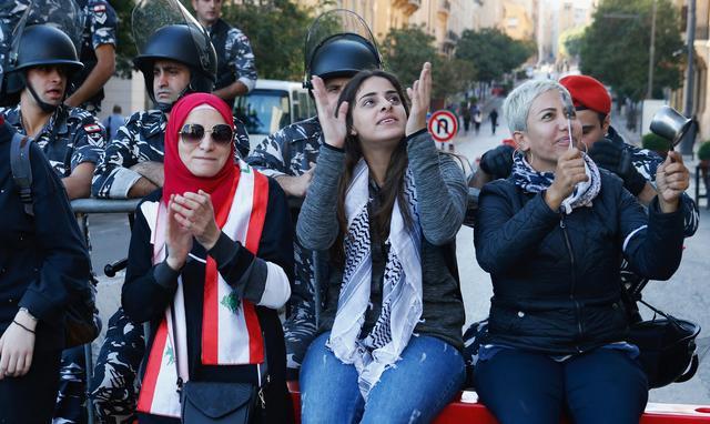 Demonstrators gesture near Lebanese police during the ongoing anti-government protest, in Beirut, Lebanon, November 19, 2019. REUTERS/Mohamed Azakir
