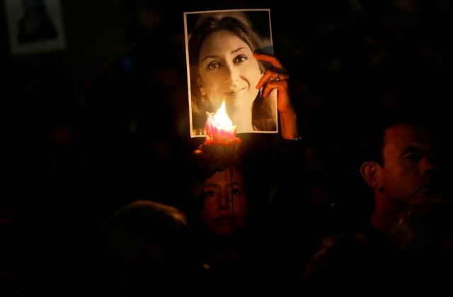 FILE PHOTO: A person holds a candle in front of a picture of anti-corruption journalist Daphne Caruana Galizia, during a vigil and protest on the second anniversary of assassination of the journalist in a car bomb, in Valletta, Malta October 16, 2019. REUTERS/Darrin Zammit Lupi/File Photo
