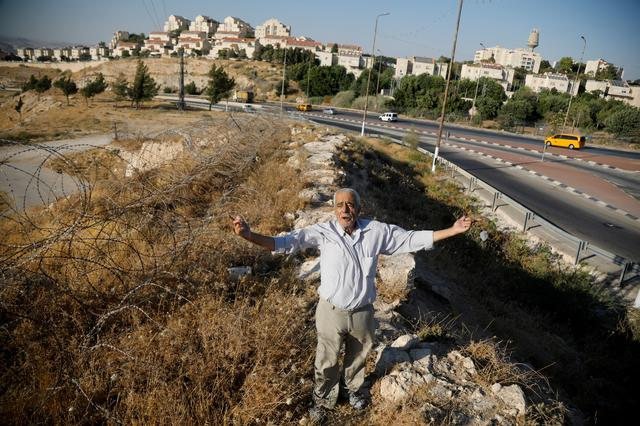 """FILE PHOTO: Palestinian man Ali Farun, 74, gestures by a road in al-Eizariya town with the Jewish settlement of Maale Adumim in the background, in the Israeli-occupied West Bank, July 27, 2019. """"It doesn't matter if they annex it to Jerusalem or if it remains West Bank - they control it man, one way or another,"""" said Farun. REUTERS/Raneen Sawafta"""