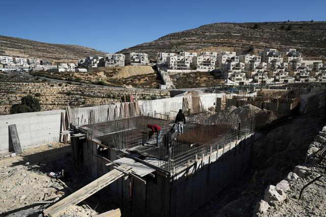 FILE PHOTO: Labourers work in a construction site in the Israeli settlement of Ramat Givat Zeev in the occupied-West Bank November 19, 2019. REUTERS/Ammar Awad/File Photo