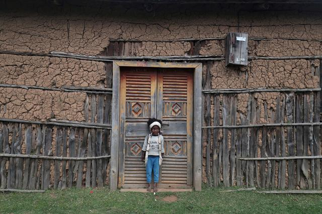A girl dressed in traditional Sidama scarf stands in front of her family's house in Wetera Rasa village near Hawassa, Ethiopia November 19, 2019. REUTERS/Tiksa Negeri