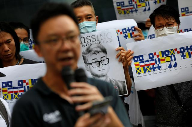 FILE PHOTO: A demonstrator holds a poster of Simon Cheng, a staff member at the consulate who went missing on August 9 after visiting the neighbouring mainland city of Shenzhen, as he and others shout slogans during a protest outside the British Consulate-general office in Hong Kong, China, August 21, 2019. REUTERS/Willy Kurniawan/File Photo