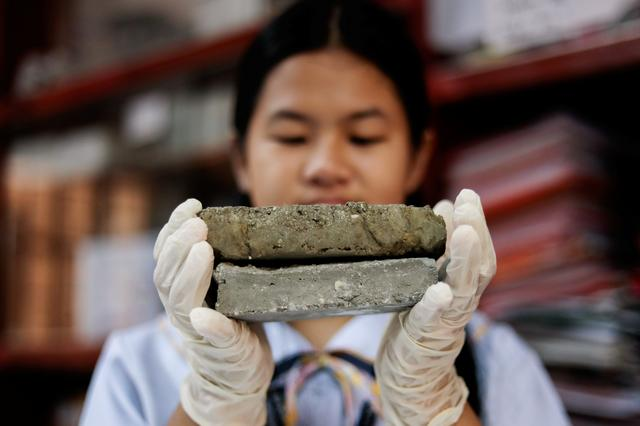 "Stephanie B. Elmido poses with her project ""Bio-bricks"" made of dog faeces and cement powder at Justice Cecilia Munoz Palma High School in Quezon City, Metro Manila, Philippines November 11, 2019. REUTERS/Eloisa Lopez"
