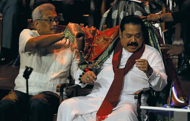 FILE PHOTO: Sri Lanka People's Front party presidential election candidate and former wartime defence chief Gotabaya Rajapaksa (L) helps his brother former president and opposition leader Mahinda Rajapaksa to remove a cloth offered by a Hindu priest during the launching ceremony of his election manifesto in Colombo, Sri Lanka October 25, 2019. REUTERS/Dinuka Liyanawatte