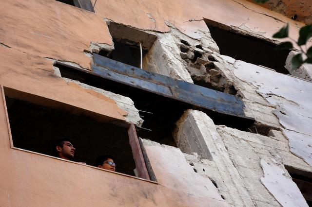 Boys look out the window of a building, damaged from an Israeli attack in Damascus, Syria November 20, 2019. REUTERS/Omar Sanadiki