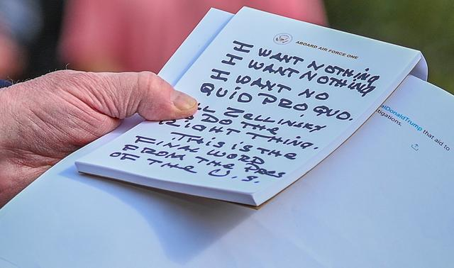 U.S. President Donald Trump holds what appears to be a prepared statement and handwritten notes after watching testimony by U.S. Ambassador to the European Union Gordon Sondland as he speaks to reporters prior to departing for travel to Austin, Texas from the South Lawn of the White House in Washington, U.S., November 20, 2019. REUTERS/Erin Scott