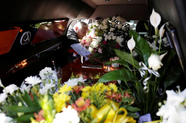 FILE PHOTO: A man puts flowers inside a hearse of one of the victims of a mass shooting at a Walmart store during a tribute in El Paso, Texas, U.S., August 18, 2019. REUTERS/Jose Luis Gonzalez