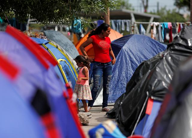 "FILE PHOTO: Central American migrants are seen outside their tents in an encampment in Matamoros, Mexico, at the end of the Gateway International Bridge, where migrants sent back under the ""Remain in Mexico"" program, officially called the Migrant Protection Protocols (MPP), await their U.S. asylum hearings, September 14, 2019. Picture taken September 14, 2019. REUTERS/Henry Romero/File Photo"