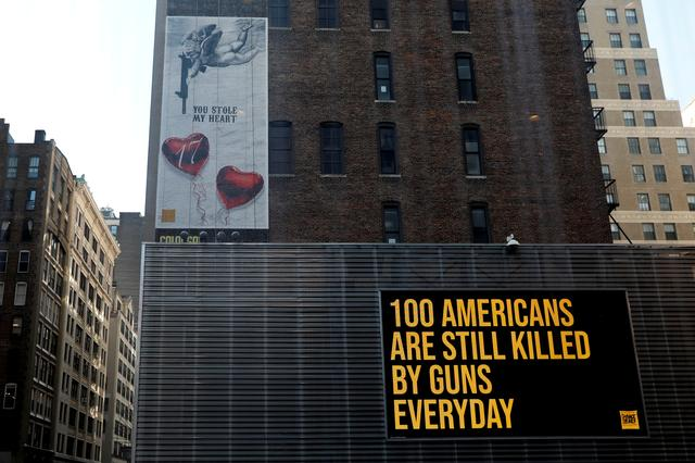 """FILE PHOTO: A """"wall of Demand"""" mural and video message created by Manuel Oliver, father of Joaquin Oliver, one of 17 people killed in the 2018 school shooting at Marjory Stoneman Douglas High School in Parkland, Florida, is seen shortly after it's unveiling on the one year anniversary of the mass shooting in New York City, New York, U.S., February 14, 2019. REUTERS/Mike Segar"""