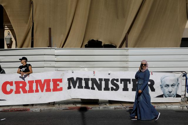 """FILE PHOTO: A woman walks past a banner depicting Israeli Prime Minister Benjamin Netanyahu and the words """"Crime Minister"""" outside the Justice Ministry as pre-trial hearings in corruption cases against Netanyahu continue, in Jerusalem October 3, 2019. REUTERS/Nir Elias"""