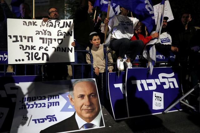 """Supporters of Israeli Prime Minister Benjamin Netanyahu protest outside his residence  following Israel's Attorney General Avichai Mandelblit's indictment ruling in Jerusalem November 21, 2019. The placards in Hebrew read, """"Mandelblit you are getting a positive coverage this evening, tomorrow you are a suspect """". REUTERS/Ronen Zvulun"""