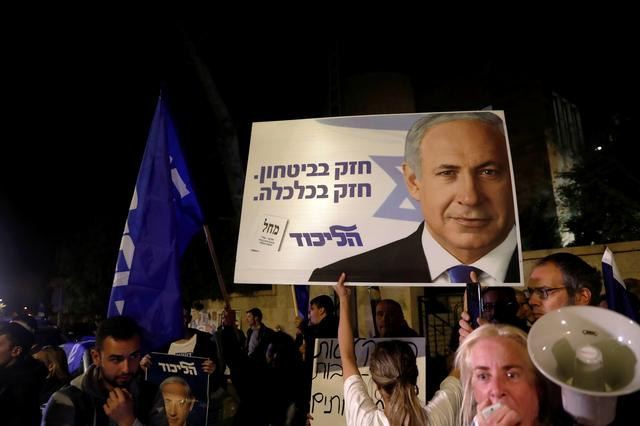 "Supporters of Israeli Prime Minister Benjamin Netanyahu protest outside his residence following Israel's Attorney General Avichai Mandelblit's indictment ruling in Jerusalem November 21, 2019. The placards in Hebrew read, ""Strong in security Strong in Economy "". REUTERS/Ronen Zvulun"