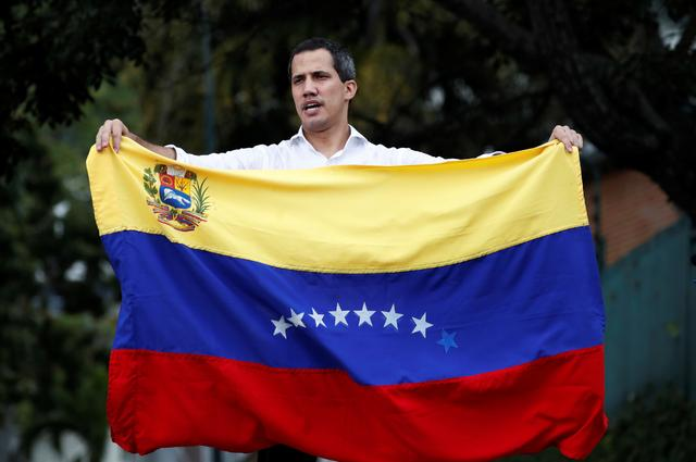 FILE PHOTO: Venezuelan opposition leader Juan Guaido, who many nations have recognised as the country's rightful interim ruler, waves the Venezuelan flag at a gathering with supporters near Bolivia's embassy in Caracas, Venezuela, November 16, 2019. REUTERS/Carlos Garcia Rawlins