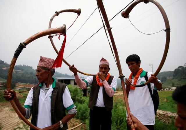 FILE PHOTO: Villagers play traditional musical instruments during an event celebrating National Paddy Day, also called Asar Pandra, that marks the commencement of rice crop planting in paddy fields as monsoon season arrives, in Dhading, Nepal, June 30, 2019. REUTERS/Navesh Chitrakar/File Photo