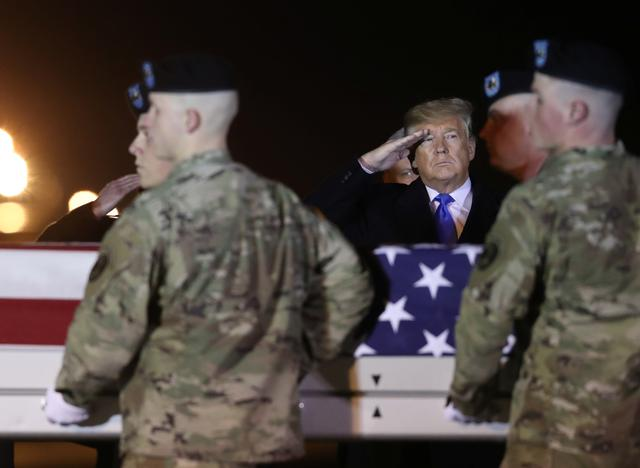 U.S. President Donald Trump salutes a transfer case holding the remains of Chief Warrant Officer David Knadle, who was killed November 20 in a helicopter crash while supporting ground troops in Afghanistan, during a dignified transfer at Dover Air Force Base, in Dover, Delaware, U.S. November 21, 2019.  REUTERS/Jonathan Ernst