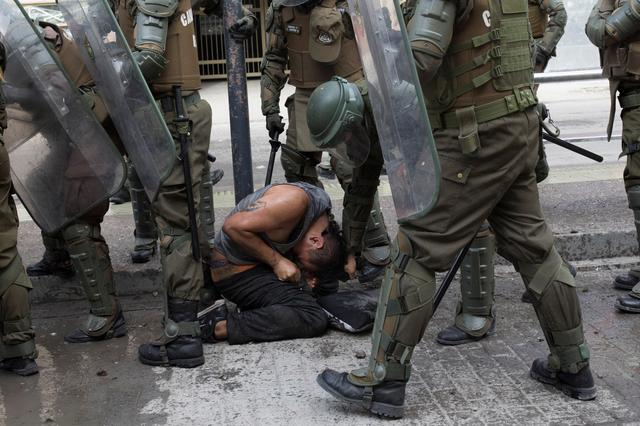 A demonstrator is pulled from his hair while is detained by riot policemen during a protest against Chile's government in Santiago, Chile, November 21, 2019. REUTERS/Pablo Sanhueza