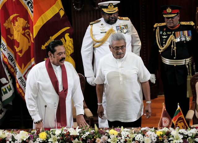 FILE PHOTO: Sri Lanka's President Gotabaya Rajapaksa and his brother and former leader Mahinda Rajapaksa, who was appointed as the new Prime Minister, look on during the swearing in ceremony in Colombo, Sri Lanka November 21, 2019. REUTERS/Dinuka Liyanawatte/File Photo