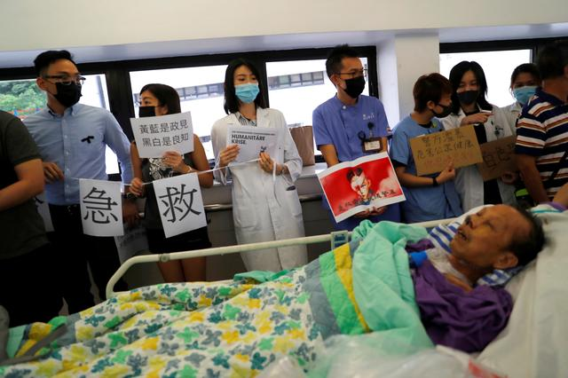 FILE PHOTO: A patient is wheeled past as healthcare staff hold posters and participate in a human chain to protest against what they say is police brutality during the anti-extradition bill protests, at Queen Mary Hospital, in Hong Kong, China, September 2, 2019. REUTERS/Anushree Fadnavis/File Photo