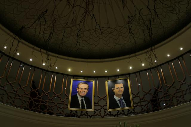 FILE PHOTO: Pictures of Syrian president Bashar al-Assad and his father Hafez al-Assad are seen inside a hotel in Damascus, Syria, September 16, 2018. REUTERS/Marko Djurica/