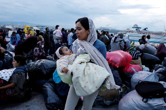 FILE PHOTO: A woman holds her baby as refugees and migrants arrive on a passenger ferry from the island of Lesbos at the port of Piraeus, Greece, October 7, 2019. REUTERS/Giorgos Moutafis/File Photo