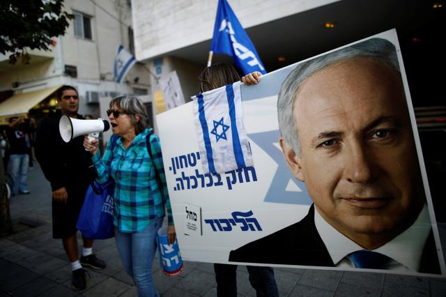 "Supporters of Israeli Prime Minister Benjamin Netanyahu protest outside Likud Party headquarters in Tel Aviv, Israel November 22, 2019. The placards in Hebrew read, ""Strong in security, strong in Economy "".  REUTERS/Corinna Kern"