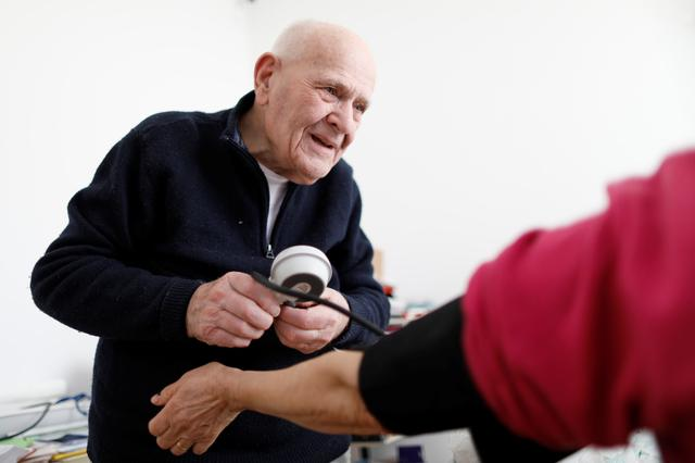 French doctor Christian Chenay, 98 years-old, treats a patient in his consulting room in Chevilly-Larue near Paris, France, November 20, 2019. Picture taken November 20, 2019. REUTERS/Charles Platiau