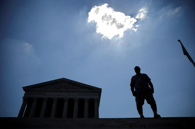 FILE PHOTO: A man stands outside the U.S. Supreme Court in Washington, U.S., June 27, 2019. REUTERS/Carlos Barria/