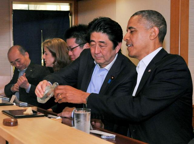 FILE PHOTO : Japanese Prime Minister Shinzo Abe pours sake for U.S. President Barack Obama as they have dinner at the Sukiyabashi Jiro sushi restaurant in Tokyo, in this picture taken April 23, 2014, and released by Japan's Cabinet Public Relations Office. Cabinet Public Relations Office/Handout via Reuters