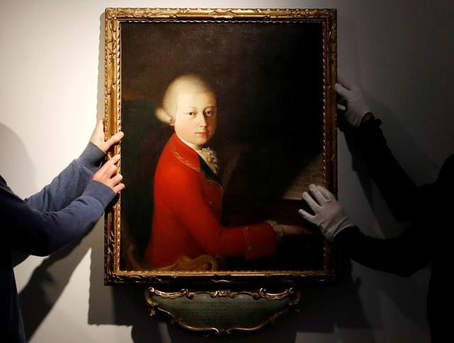 FILE PHOTO: Workers install a portrait due to be sold at auction by Christie's on November 27 which depicts composer Wolfgang Amadeus Mozart as a teenager, painted in January 1770, and attributed to Veronese master Gaimbettino Cignaroli, in Paris, November 12, 2019. REUTERS/Christian Hartmann/File Photo